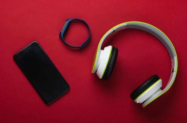 스마트 폰이있는 세련된 스테레오 헤드폰, 빨간색 표면의 스마트 팔찌