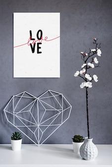アパート内のスタイリッシュな静物。内部のコンクリートの壁の背景に関するノートとエレガントな透かし彫りハート。ミニマリズム。愛とバレンタインデーのコンセプトシンボル。室内装飾