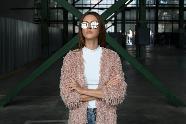 Stylish street look up fashion tall model long brown hair woman in sunglasses with mirror effect in pink coat and white shirt poses with hands crossed in industrial storage parking fabric manufacture