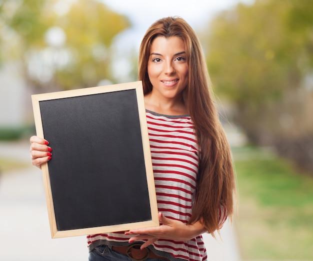 작은 칠판을 들고 세련 된 학생 소녀