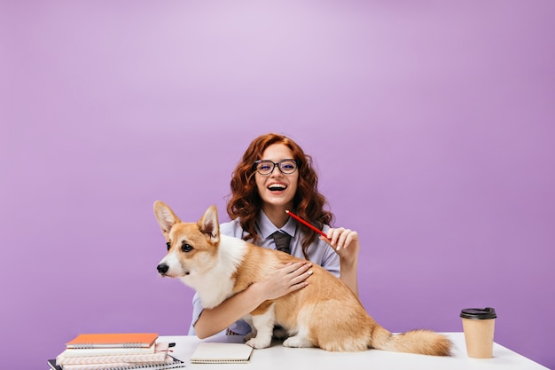 Stylish student girl hugging corgi on purple wall