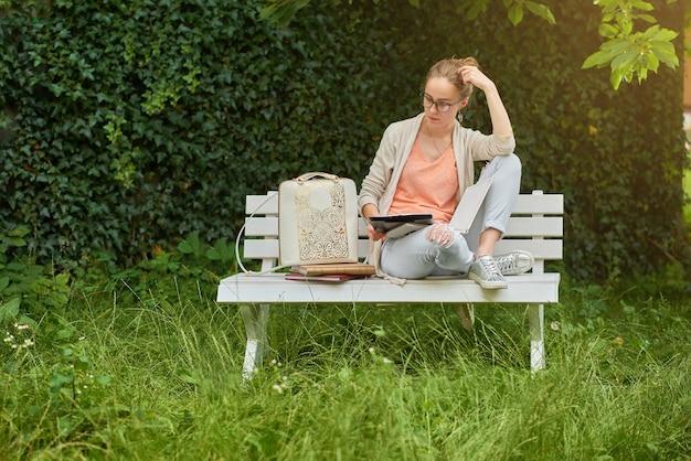 Стильная студентка учится на скамейке в белом парке. рядом с ней разные книги и модный рюкзак с золотым узором. на ней очки, синие джинсы, легкая футболка.
