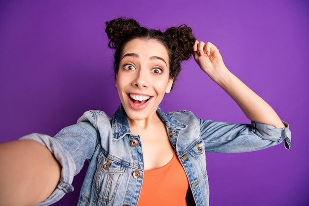 Stylish student with curly hair posing against the purple wall