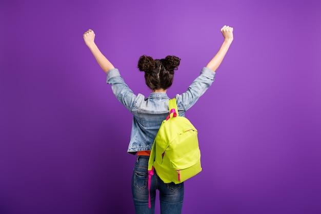 Стильная студентка с вьющимися волосами позирует у фиолетовой стены