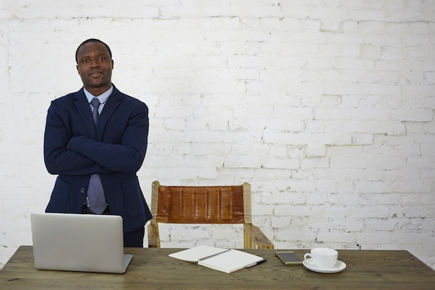 Stylish successful african american male entrepreneur having confident look standing at his workplace against white brick wall with copy space for your text or promotional information
