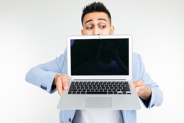 Stylish successful man in a jacket demonstrates a laptop screen with space for advertising on a white studio background