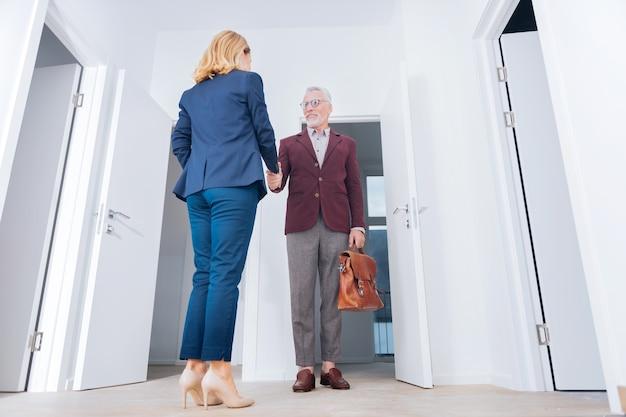 スタイリッシュなスーツ。彼の魅力的なエレガントな女性のパートナーの手を振るスタイリッシュなスーツを着てひげを生やした成熟したビジネスマン