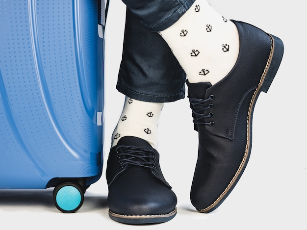 Stylish suitcase, men's legs and bright socks