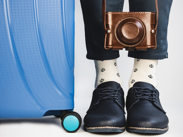Stylish suitcase, men's legs, vintage camera and bright socks