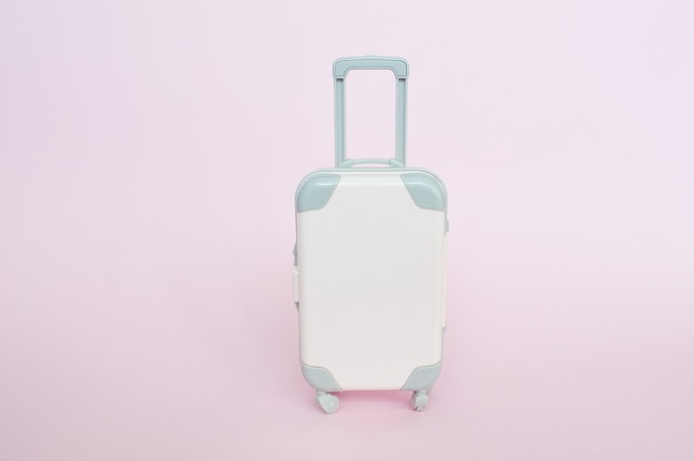 Stylish suitcase on pink background