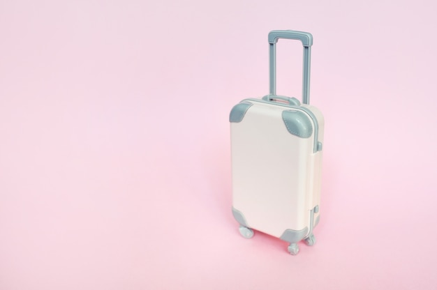 Stylish suitcase on pink, top view with copyspace. concept for travel