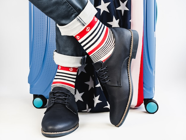 Stylish suitcase, us flag, men's legs and bright socks