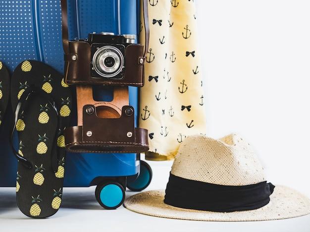 Stylish suitcase, vintage camera and sun hat