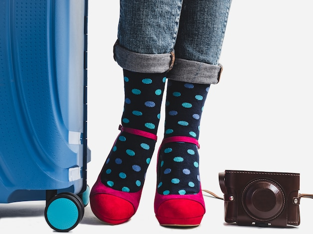 Stylish suitcase, women's legs and bright socks