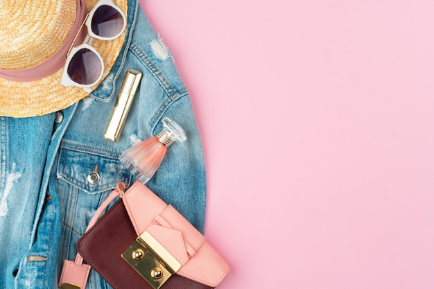 Stylish summer outfit for woman on pastel pink background