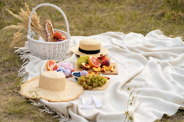 Stylish summer picnic on a white blanket.