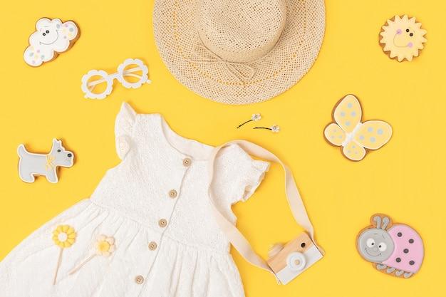 세련된 여름 아동복 세트입니다. 노란색 바탕에 흰색 드레스, 밀짚모자, 선글라스, 액세서리. 패션 소녀 룩북 개념입니다. 평면도 평면도.