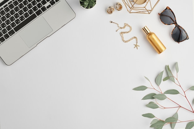 Stylish sunglasses, bottle of scent, golden earrings and chain, small domestic plant, branch with green leaves and laptop keypad on desk
