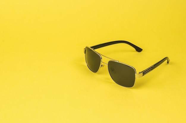 黄色の背景の男性のためのスタイリッシュなサングラス。ファッショナブルなメンズアクセサリー。