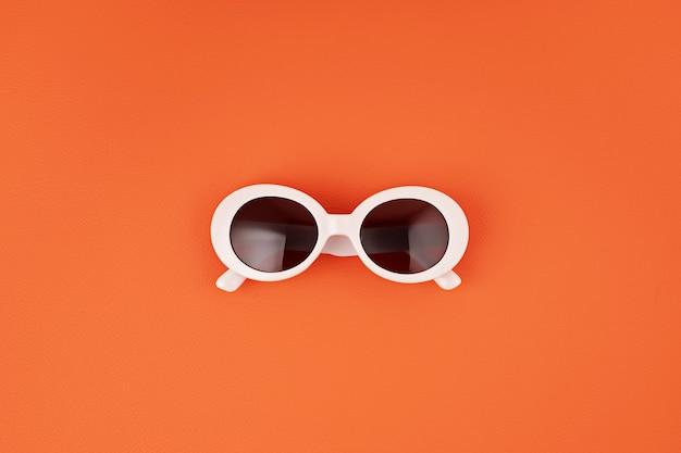 オレンジ色の壁にスタイリッシュなサングラス。夏のファッション、パーティー、夏のスタイル、休暇のコンセプト。最小限のフラットレイ、上面図