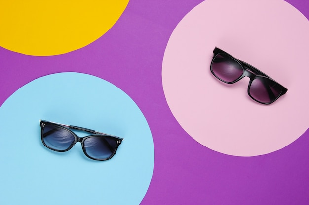 Stylish sunglasses on purple with colored paper circles
