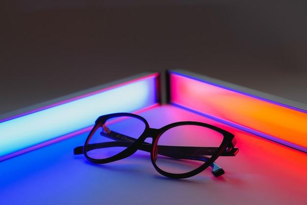 Стильные солнцезащитные очки, снятые с использованием розового и синего абстрактного цветного освещения с копией пространства.