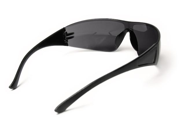 Stylish sunglasses on a white wall