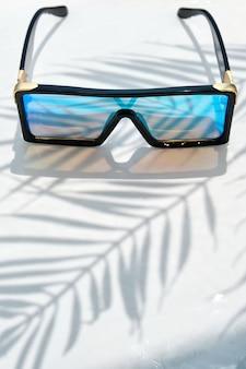 ミラーリングされたメガネとスタイリッシュなサングラスは、水の背景に横たわっています。ヤシの木の影。コピースペースとレジャー、旅行、エンターテインメントのコンセプト