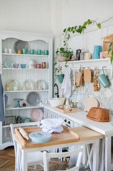 Stylish and sunny interior of kitchen space with small wooden table at the photo studio. scandinavian room decor with kitchen accessories.