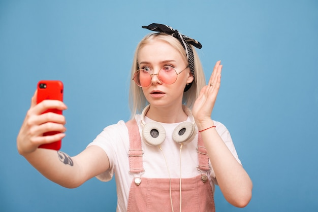 Stylish surprised girl in a bright casual clothing and pink glasses stands on a blue background with a smartphone in her hands and looks shocked at the phone screen