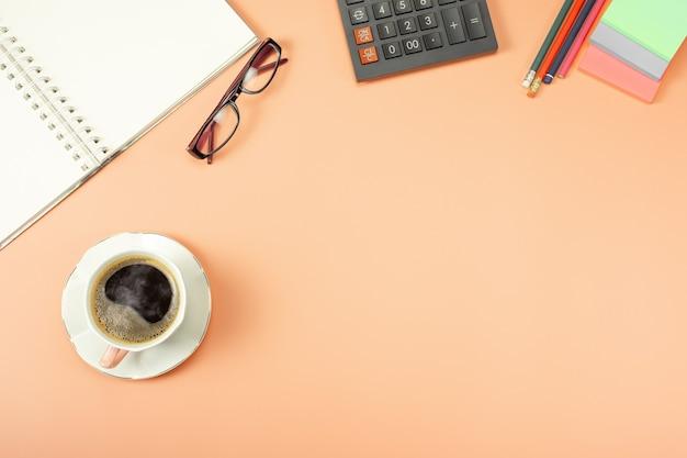 スタイリッシュなテーブルデスク、ワークスペース。モダンなデスクを備えたオフィスの職場。メモ帳とコーヒーと電卓の上からの上面図。 Premium写真