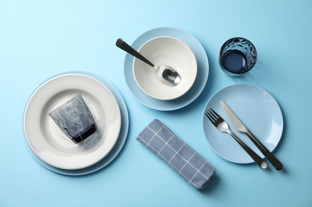 Stylish table setting on blue background, top view