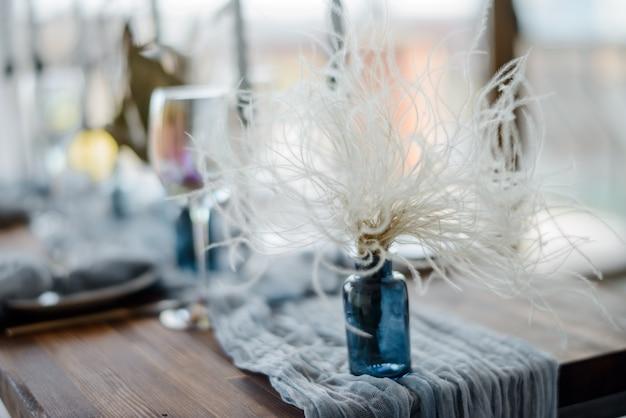 세련된 테이블 세팅. 결혼식 장식. 아름 다운 밝은 파란색 거 즈 식탁보와 곱슬 흰색 말린 된 꽃과 작은 꽃병 나무 테이블. 선택적 초점