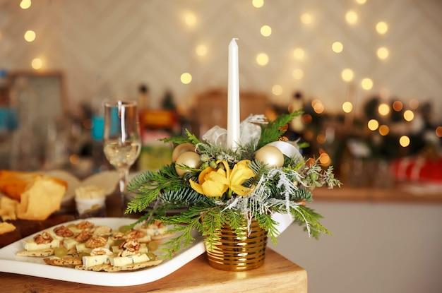 Стильная сервировка стола с зажженными свечами и елочными украшениями. роскошный романтический обеденный стол при свечах для пары. фужеры и красивое украшение еды. романтический изысканный ужин