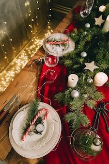 ろうそくやクリスマスの飾りが付いたスタイリッシュなテーブルセッティング