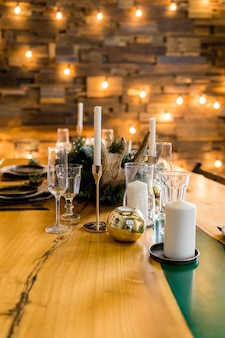 Stylish table setting with burning candles and christmas decorations.beautiful table setting with christmas decorations in living room. festive decoration on table, romantic holiday evening