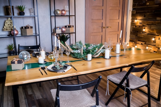 Stylish table setting with burning candles,festive decorations.beautiful living room decorated for christmas and new year with stylish table set for four person and vintage christmas decoration.