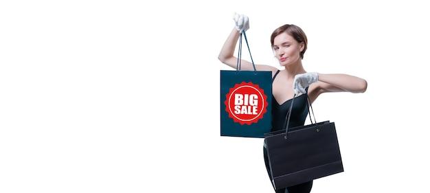 Стильная высокая девушка в белых перчатках демонстрирует роскошный черный пакет