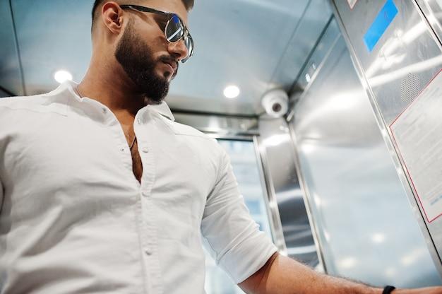 Стильный высокий мужчина в белой рубашке и темных очках позирует у лифта внутри