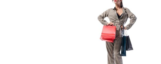 パッケージでポーズをとるスタイリッシュな背の高い女性。ノーネーム。白色の背景。割引、販売、購入のコンセプト。ミクストメディア