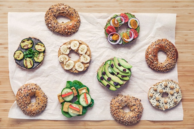 Stylish and tasty composition of vegan and vegetarian sandwiches with vegetables herbs paste seeds hummus egg cheese and lettuce fresh and healthy breakfast copy space wooden table top view