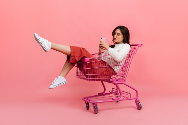 Stylish teen girl in culottes and white sweater sits in supermarket trolley. model in glasses sends kiss and makes selfie on pink.