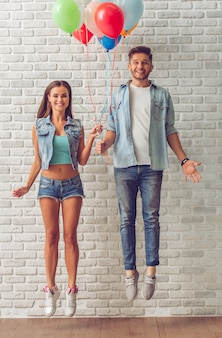 Stylish teenage couple holding balloons and jumping
