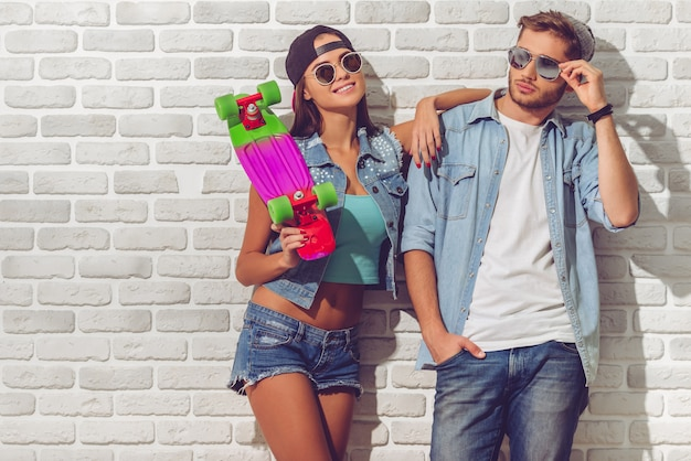 Stylish teenage couple in jean clothes, caps and sun glasses