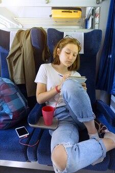 Стильная девочка-подросток едет на поезде. рисует и слушает музыку