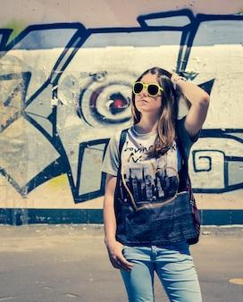 Stylish teenage girl in sunglasses posing near graffiti wall