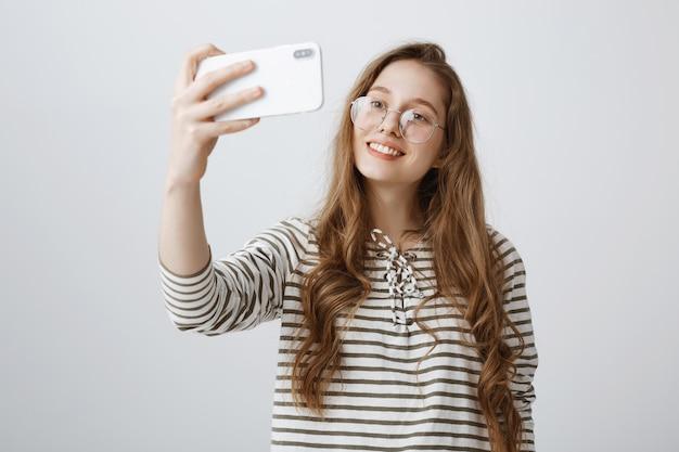 Elegante ragazza adolescente prendendo selfie sullo smartphone, sorridendo felice
