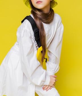 Стильная девушка-подросток на желтом фоне в белой рубашке и желтой поясной сумке