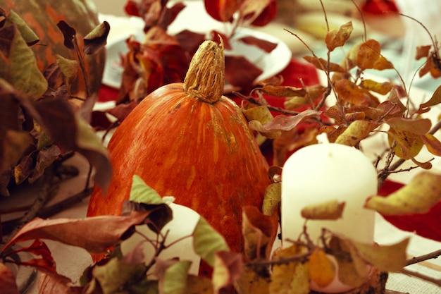 カボチャと乾燥した枝のあるスタイリッシュな感謝祭の秋のテーブルの装飾