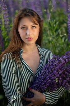 一握りのルピナスの花でポーズをとる縞模様のドレスのスタイリッシュな思いやりのある女の子